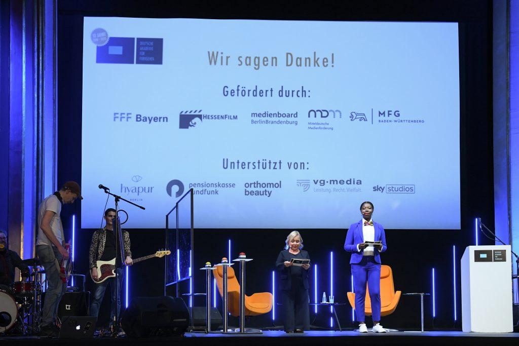 """Wir sehen eine Bühne mit Zuschauerraum. Auf der Bühne links die Band """"Theodor Shitstorm"""" in der Mitte Moderatorenduo ChrisTine Urspruch und Dayan Kodua vor einer Leinwand. Auf der Leinwand Sponsorenlogos"""