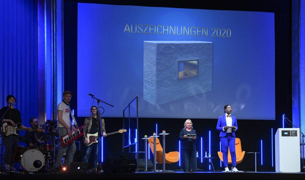 """Wir sehen eine Bühne mit Zuschauerraum. Auf der Bühne links die Band """"Theodor Shitstorm"""" in der Mitte Moderatorenduo ChrisTine Urspruch und Dayan Kodua vor einer Leinwand. Auf der Leinwand steht """"Auszeichnungen 2020"""""""