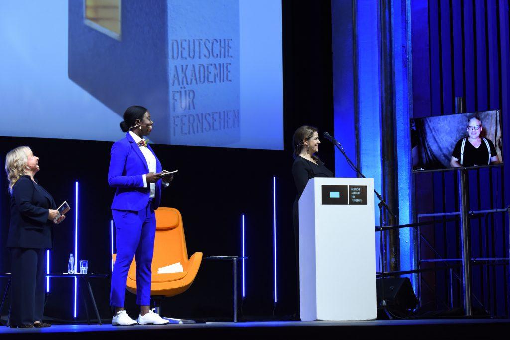Wir sehen eine Bühne, links Moderatorin ChrisTine Urspruch und Dayan Kodua und Laudatorin Rebecca Immanuel, rechts einen Monitor mit dem Preisträger der Kategorie Bildgestaltung