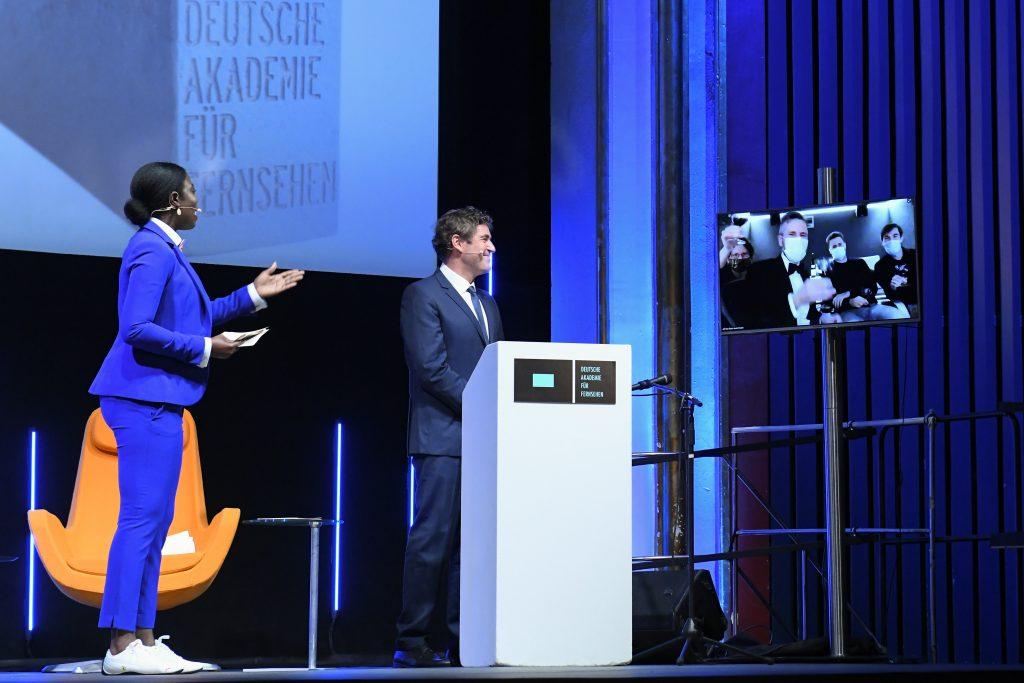 Wir sehen eine Bühne, links Laudator Stephan Szazsz und Moderatorin Dayan Kodua, rechts einen Monitor mit dem Preisträger der Kategorie Tongestaltung