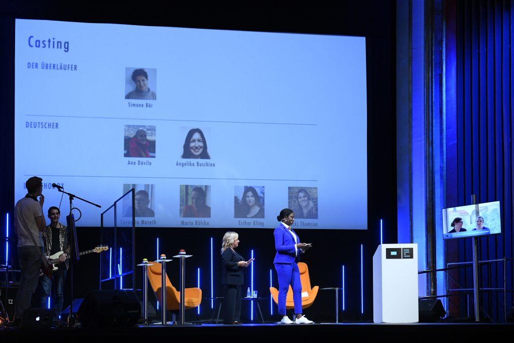 Wir sehen eine Bühne, links eine Band, in der Mitte das Moderatorenduo vor Leinwand. Auf der Leinwand sehen wir Bilder der Nominierten der Kategorie: Casting