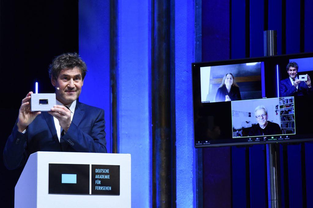 Wir sehen eine Bühne, links Laudator Stephan Szasz und rechts einen Monitor mit den Preisträgern
