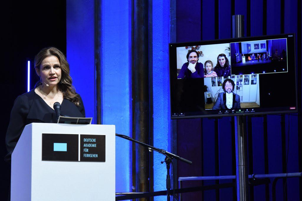 Wir sehen eine Bühne, links Laudatorin Rebecca Immanuel und rechts einen Monitor mit dem Preisträger