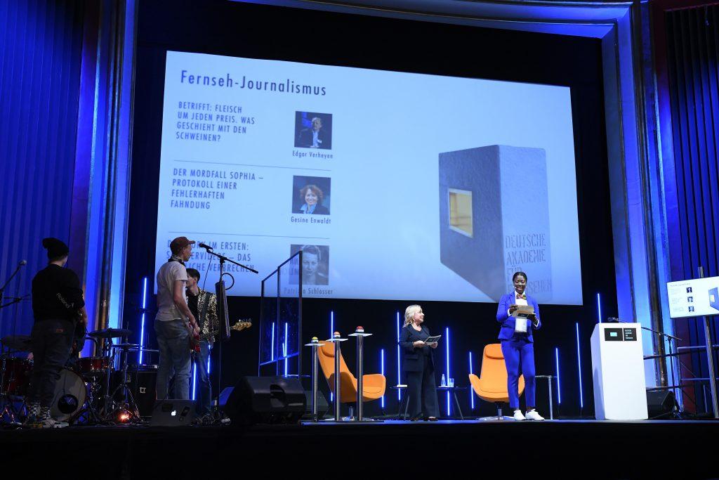 Wir sehen eine Bühne, links eine Band, in der Mitte das Moderatorenduo vor Leinwand. Auf der Leinwand sehen wir Bilder der Nominierten