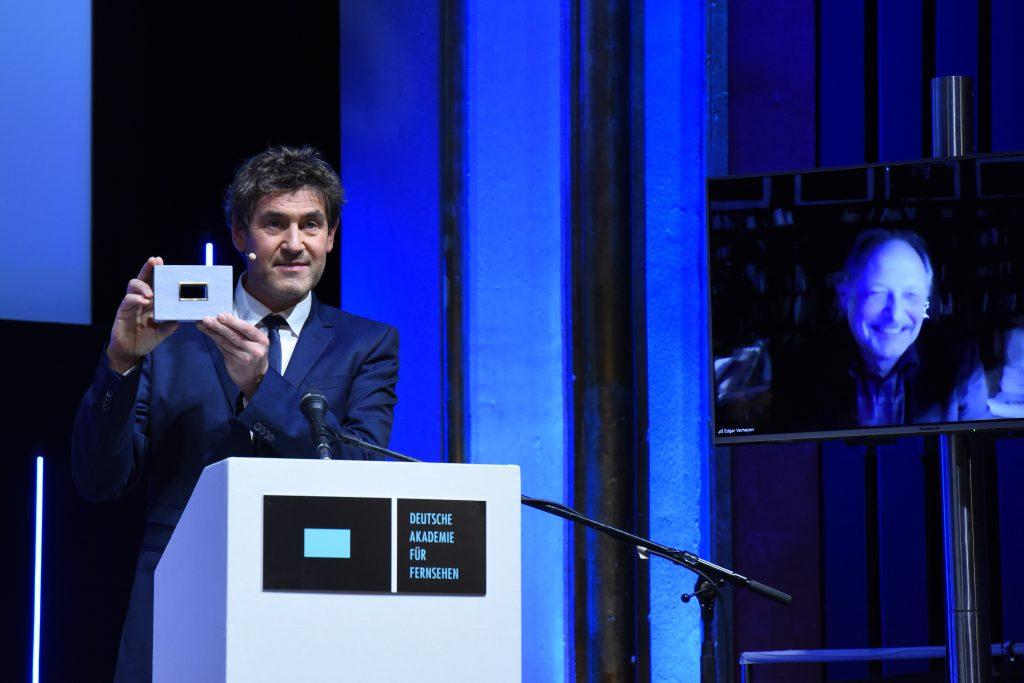 Wir sehen eine Bühne, links Laudator Stephan Szasz und rechts einen Monitor mit dem Preisträger