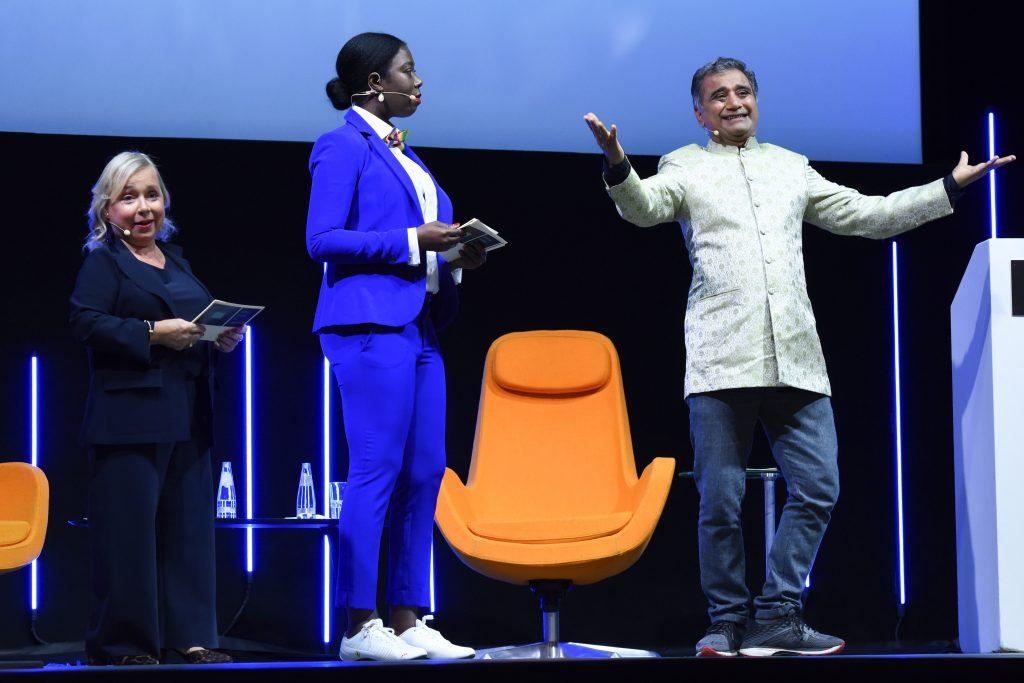 Wir sehen eine Bühne mit 3 Menschen