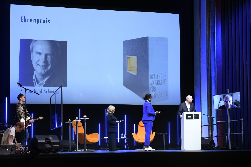 Wir sehen eine Bühne, in der Mitte die Moderatorinnen und Vorstandsmitglied Stephan Ottenbruch und rechts einen Monitor mit der Preisträger