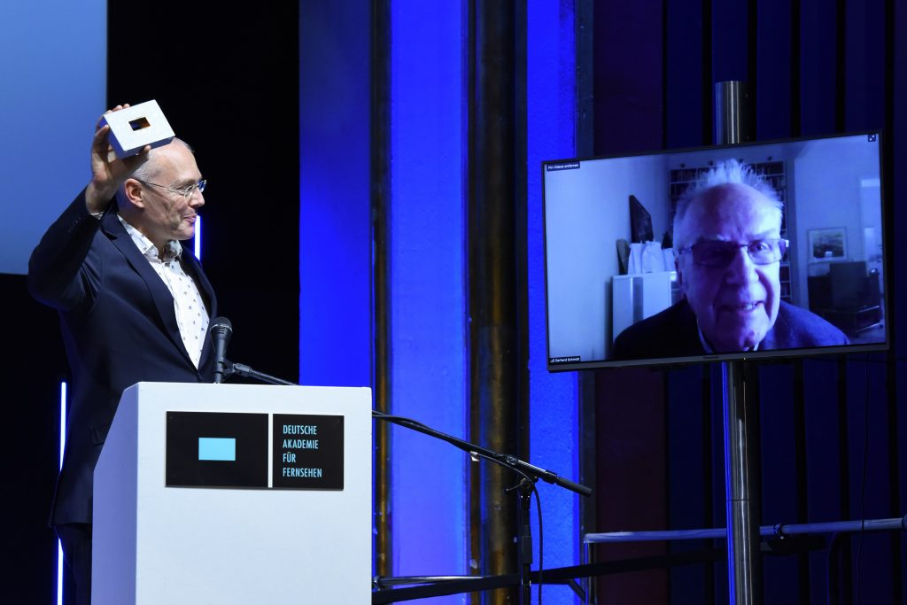 Wir sehen eine Bühne, links Vorstandsmitglied Stephan Ottenbruch und rechts einen Monitor mit der Preisträger