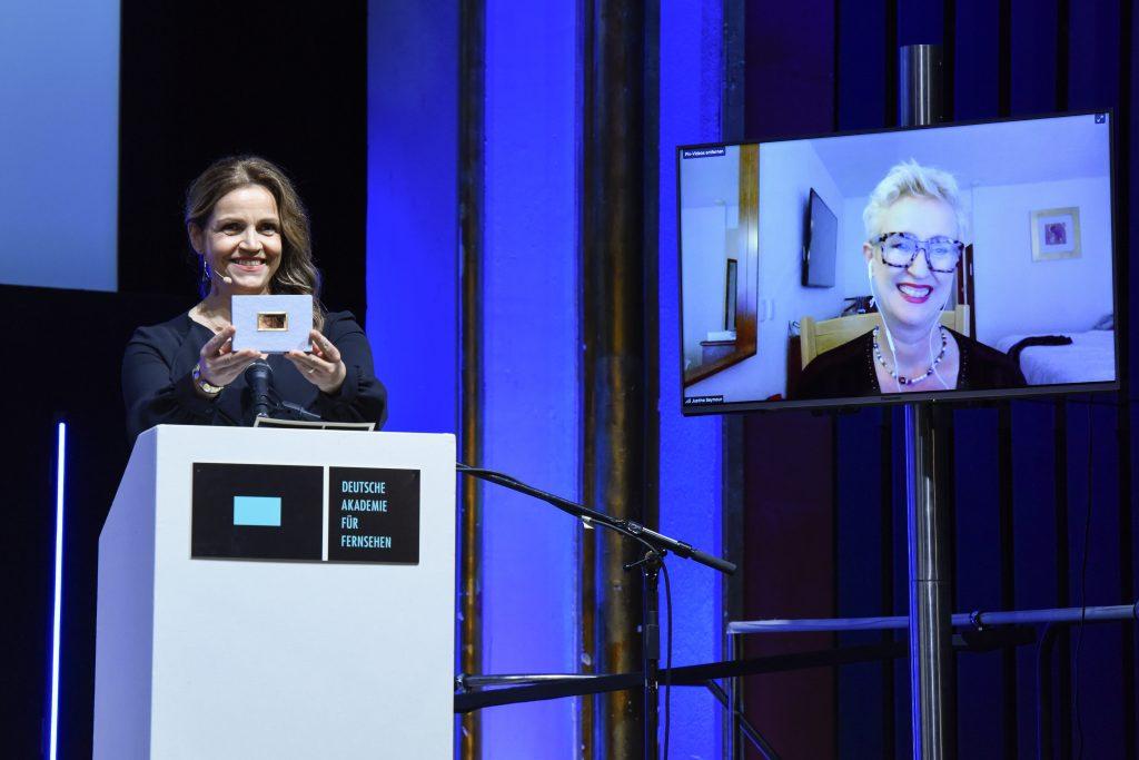 Wir sehen eine Bühne, links Laudatorin Rebecca Immanuel und rechts einen Monitor mit der Preisträgerin