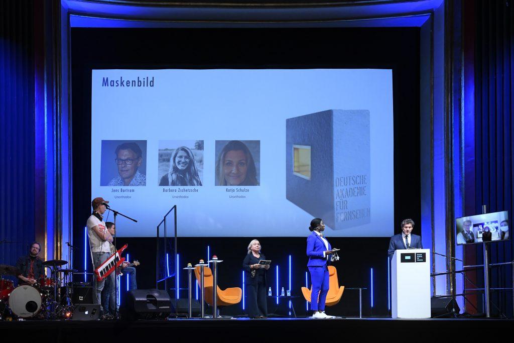 wir sehen eine Bühne. Links die Band, in der Mitte das Moderatorenduo vor der Leinwand mit den Preisträgern, rechts einen Bildschirm mit den Preisträgern