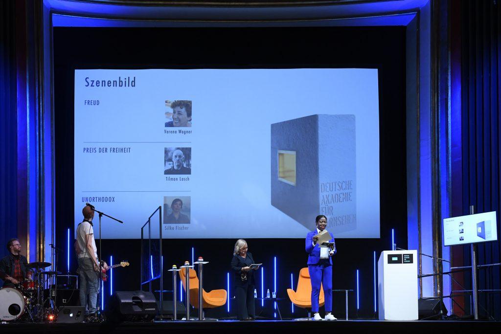 wir sehen eine Bühne. Links die Band, in der Mitte das Moderatorenduo vor der Leinwand mit allen Nominierten, rechts einen Bildschirm mit allen Nominierten