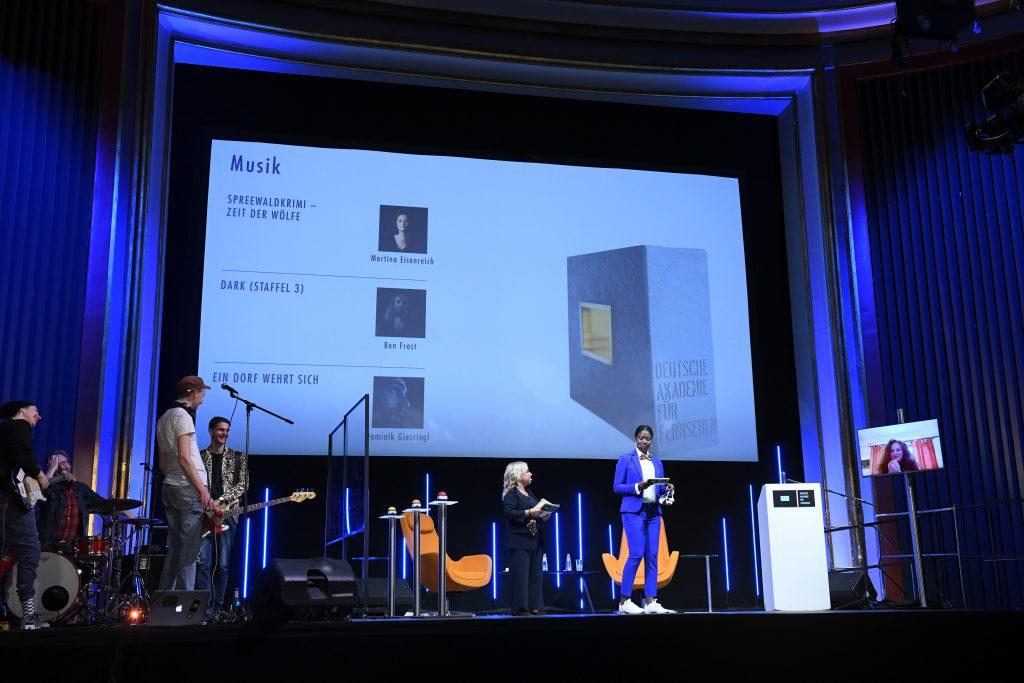 wir sehen eine Bühne. Links die Band, in der Mitte das Moderatorenduo vor der Leinwand mit allen Nominierten, rechts einen Bildschirm mit der Preisträgerin.