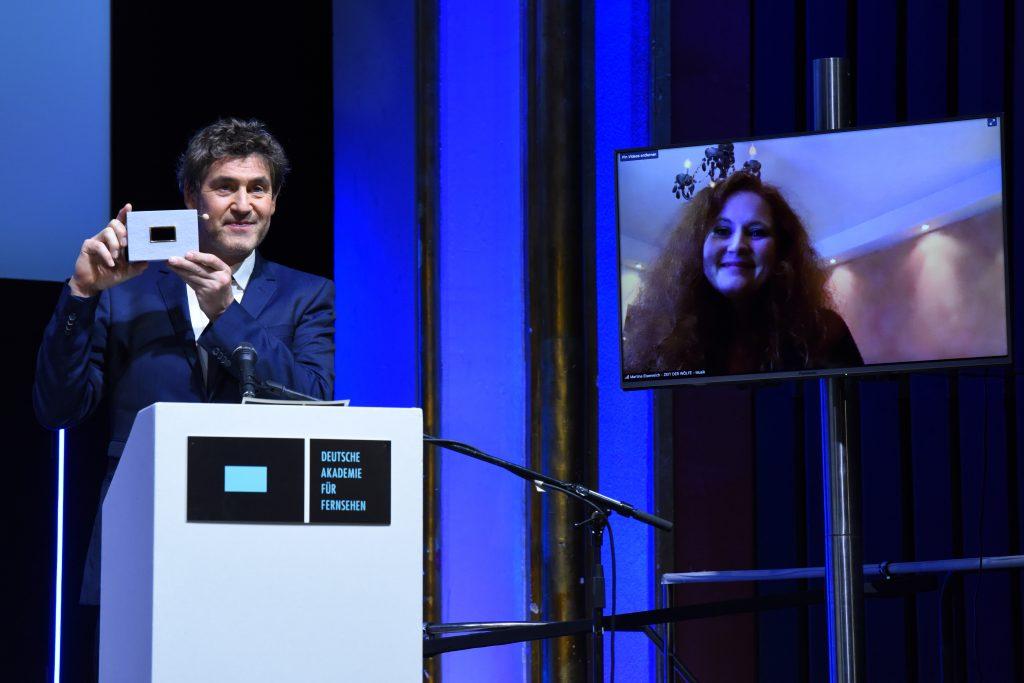 Wir sehen eine Bühne, links Laudator Stephan Szasz und rechts einen Monitor mit der Preisträgerin