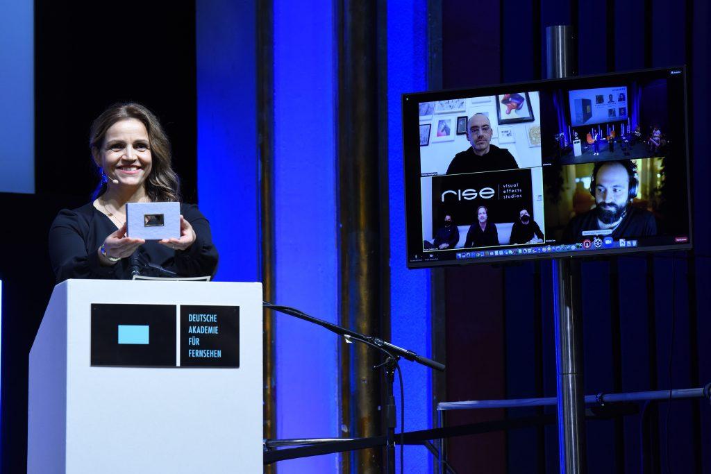 wir sehen links Laudatorin Rebecca Immanuel und rechts einen Monitor mit den Nominierten