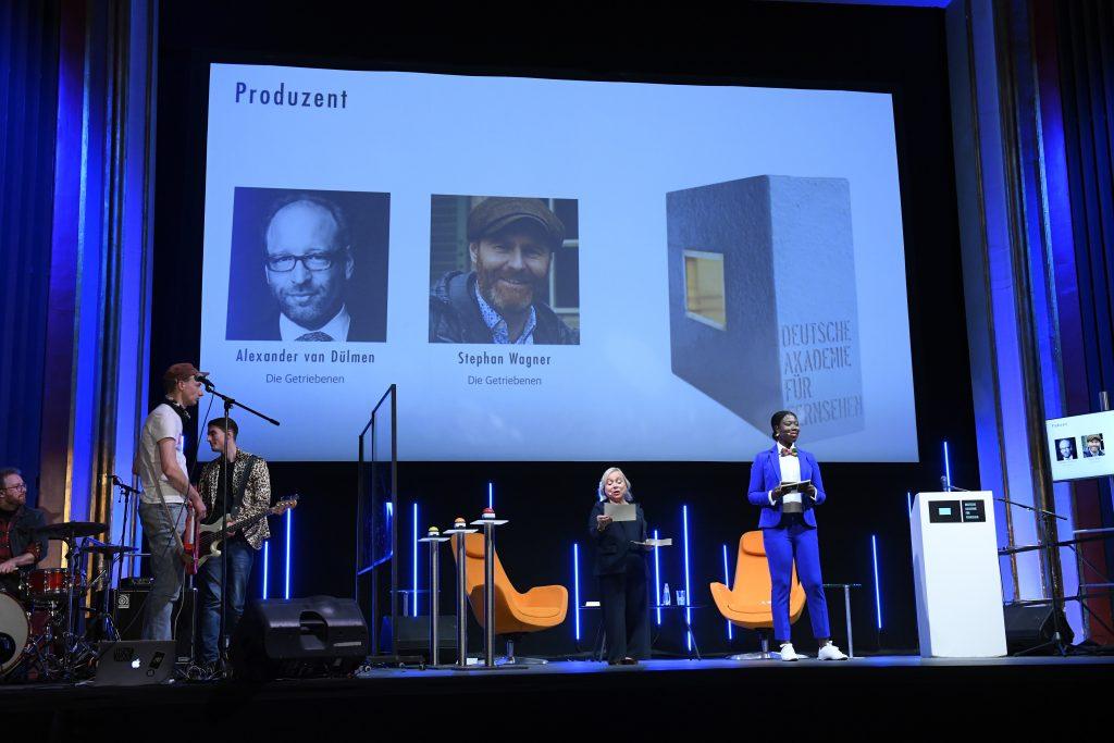 wir sehen eine Bühne. Links die Band, in der Mitte das Moderatorenduo, rechts einen Bildschirm mit den Preisträgern. Auf der Leinwand sehen wir ein Fotos der Preisträger