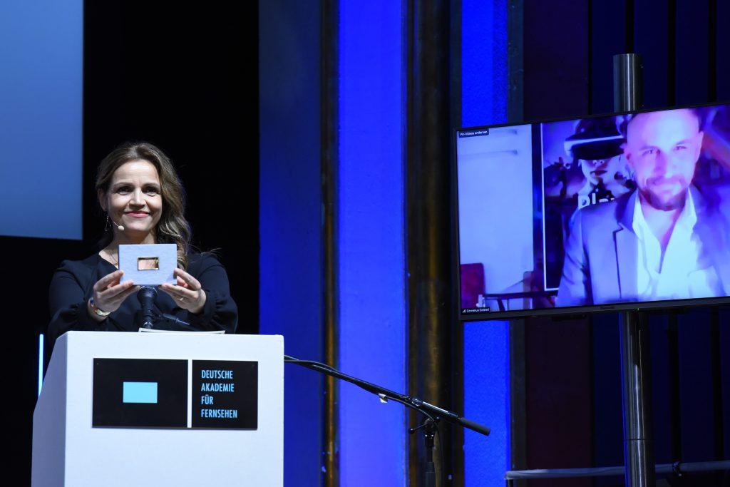 wir sehen eine Bühne. Links die Laudatorin Rebecca Immanuel, rechts einen Bildschirm mit dem Preisträger.
