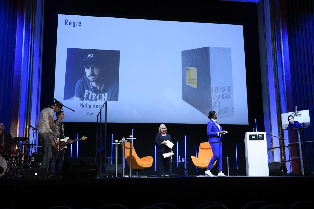 wir sehen eine Bühne. Links die Band, in der Mitte das Moderatorenduo, rechts einen Bildschirm mit dem Preisträger. Auf der Leinwand sehen wir ein Fotos des Preisträgers