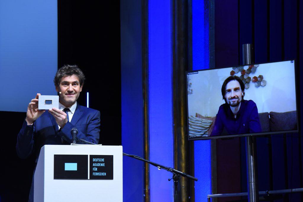 wir sehen eine Bühne. Links den Laudator Stephan Szasz, rechts einen Bildschirm mit dem Preisträger.