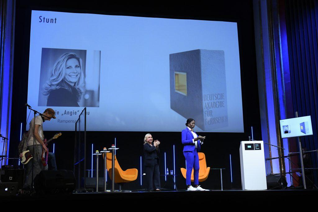 wir sehen eine Bühne. Links die Band, in der Mitte das Moderatorenduo, rechts einen Bildschirm mit dem Preisträgerin. Auf der Leinwand sehen wir ein Fotos der Preisträgerin