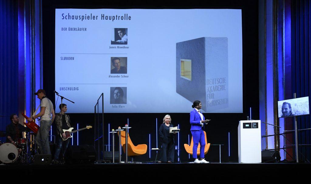 wir sehen eine Bühne. Links die Band, in der Mitte das Moderatorenduo, rechts einen Bildschirm mit dem Preisträger. Auf der Leinwand sind Fotos der Nominierten zu sehen.