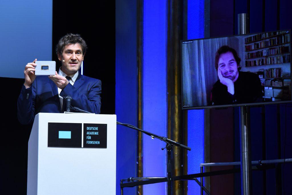 Wir sehen links den Laudator, der den Preis übergibt. Rechts ist ein Monitor auf dem den Preisträger Felix Klare zu sehen ist.