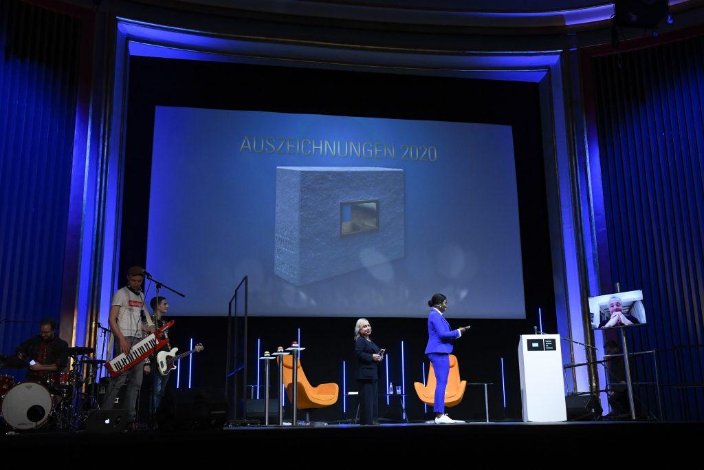 Wir sehen eine Bühne: links die Band, in der Mitte Moderatoren und rechts einen Bildschirm
