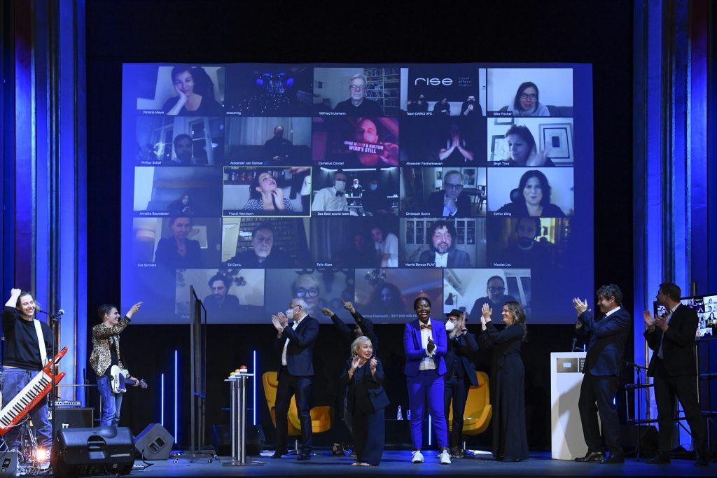 Wir sehen Moderatoren, Band, Laudatoren auf der Bühne vor einer Leinwand. Auf der Leinwand sind die Preisträger 2020 zu sehen