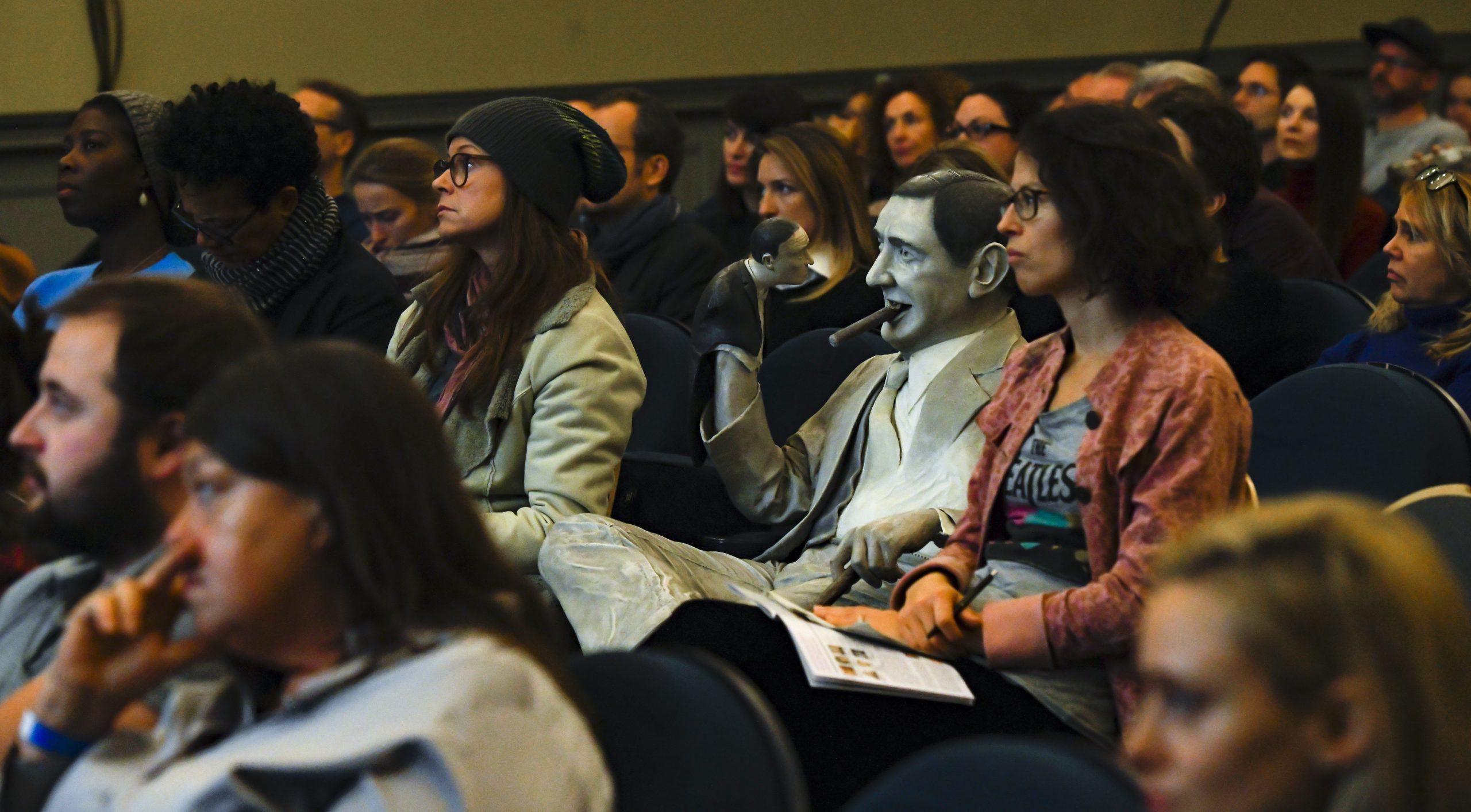 wir sehen ein Publikum mit Ernst Lubitsch Statue in der Mitte