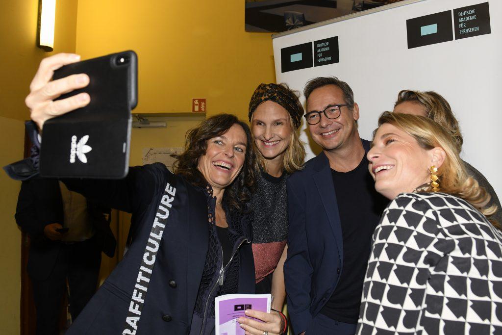 wir sehen eine Gruppe Menschen vor einer Pressewand die ein Selfie machen