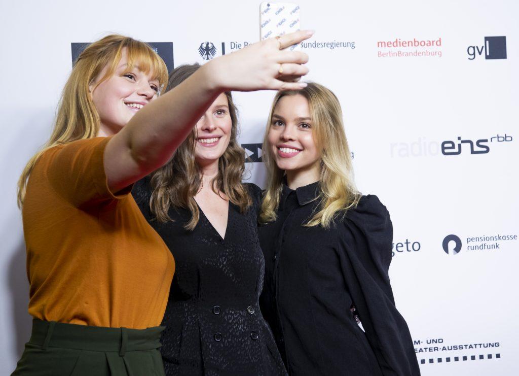Wir sehen 3 Frauen die ein Selfie vor einer Pressewand machen