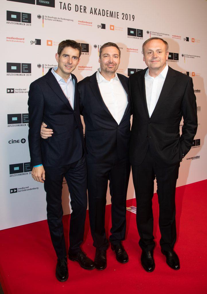 Wir sehen 3 Männer vor einer Pressewand